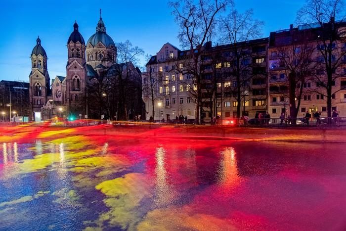 """""""THE BURNING RIVER""""  Installation des Künstlers Jan Kuck in München (7.-15.3.2020). zur blauen Stunde. Im Hintergrund die St. Lukas Kirche."""